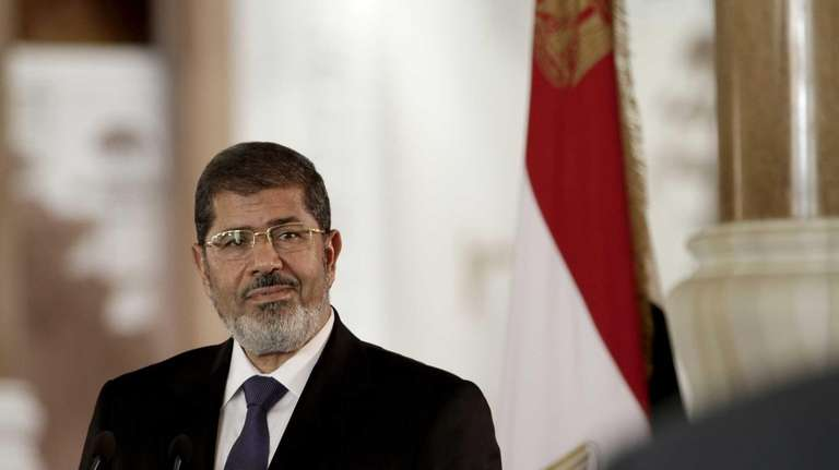 Egyptian President Mohammed Morsi speaks to reporters during