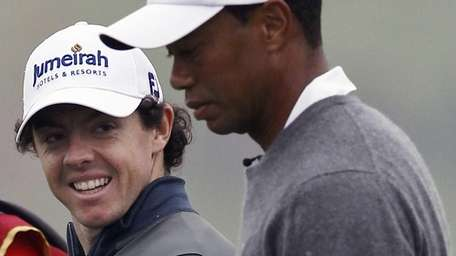 Tiger Woods, right, and Rory McIlroy walk together