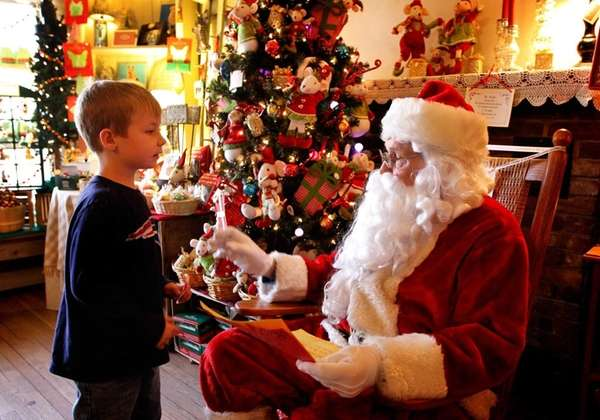 Drew Wimmer, 6, of Huntington, gives Santa his