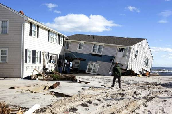 People survey damage to beachfront houses in Long