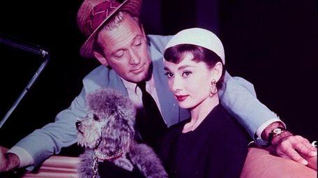 Audrey Hepburn as Sabrina Fairchild holds a poodle