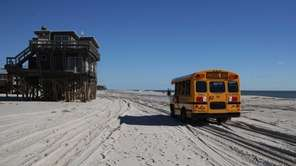 A school bus passes a home damaged by