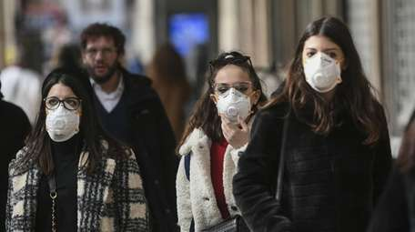 People in Milan, Italy, wear masks to ward