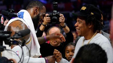 Lakers forward LeBron James, left, greets rapper Jay-Z