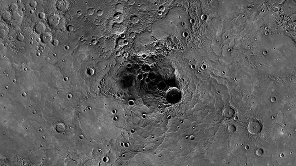 A 68-mile-diameter crater, large indentation at center, in