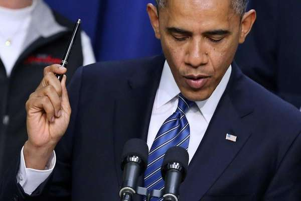 President Barack Obama holds a pen while saying