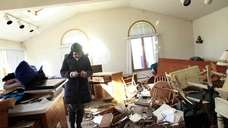 A woman sifts through her mother's damaged home