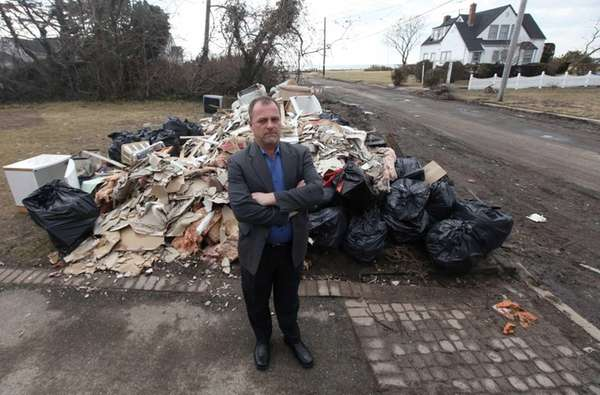 Michael Gramse stands before a pile of garbage