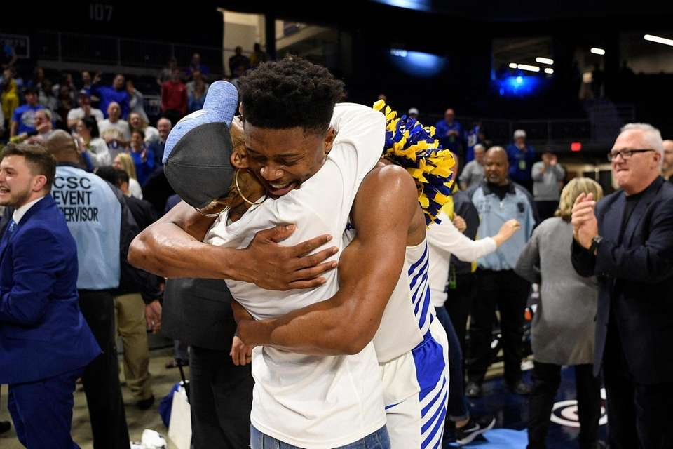 Hofstra guard Eli Pemberton, right, hugs a fan