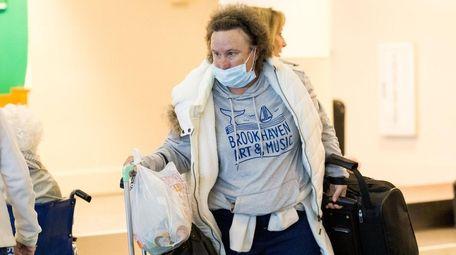Kathy Behrens of Mastic Beach retrieves her baggage