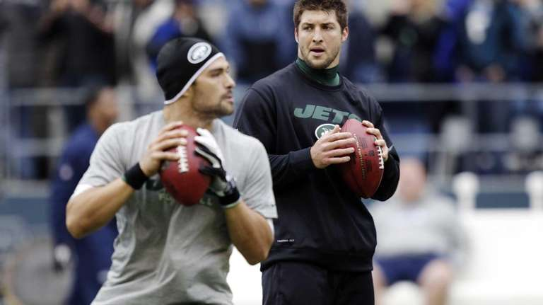 Tim Tebow, right, watches as Mark Sanchez, left,