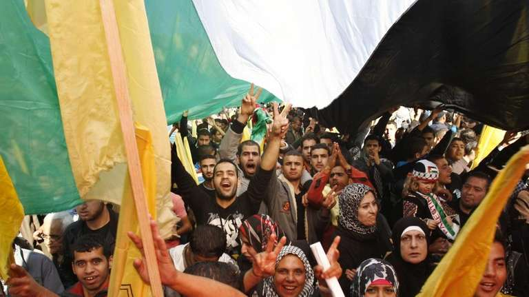 Palestinians wave Fatah and Palestinian flags during a