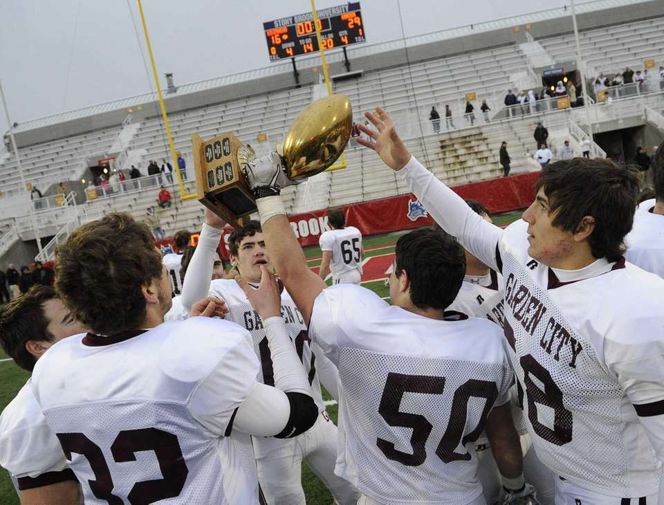 Garden City players reach for the championship trophy