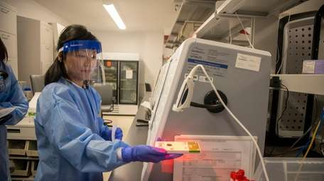Ka Wai Chan, a medical technologist, conducts tests