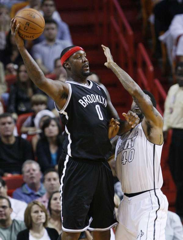 Andray Blatche passes the ball past Miami Heat