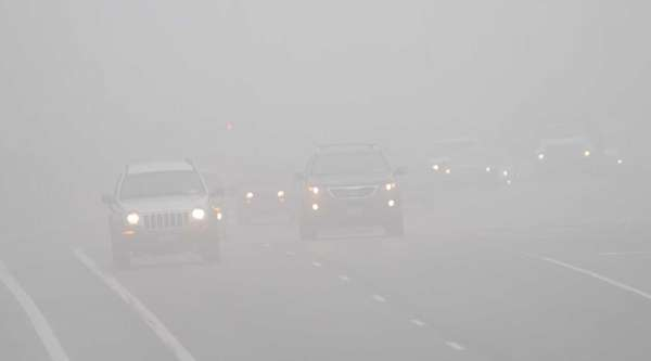 Drivers make their way through dense fog along