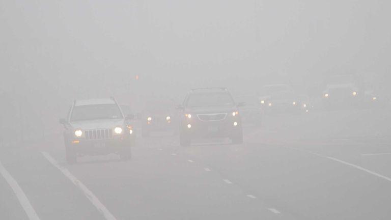 Drivers make their way through dense fog along