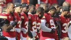 Kansas City Chiefs players stand arm-in-arm during a