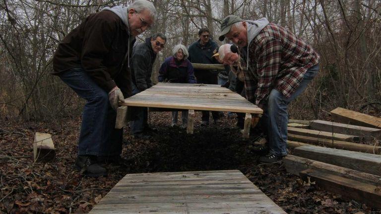 Volunteers work in Heckscher State Park to repair