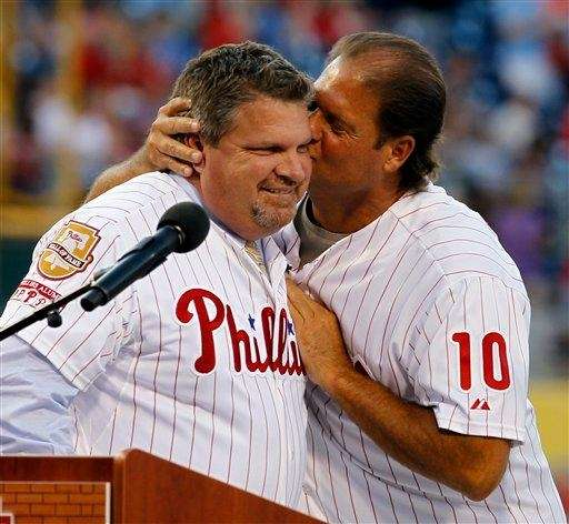 Ex-Philadelphia Phillies player John Kruk, left, is kissed