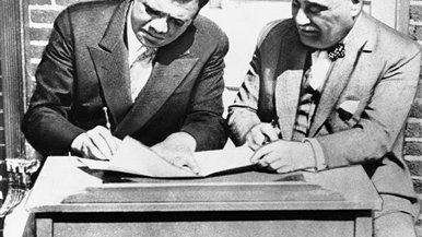 At right, Babe Ruth, seated left, signs a