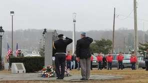 Two men salute wreathes laid in honor of