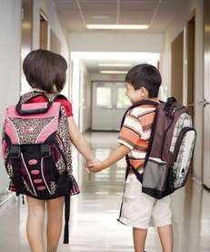 Two little school kids experiencing puppy love, holding