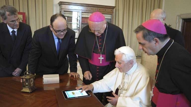 Pope Benedict XVI uses a touchpad to send