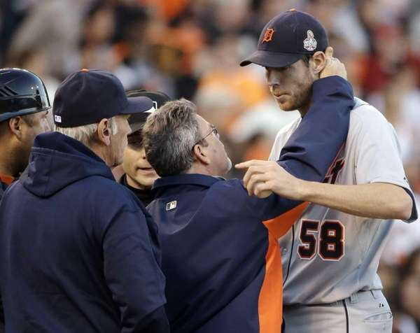 A trainer looks at Detroit Tigers starting pitcher