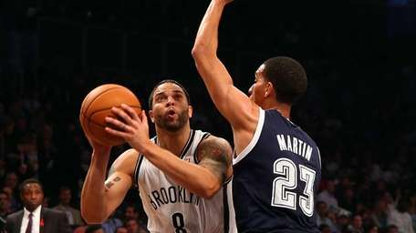 Deron Williams attempts a shot in front of