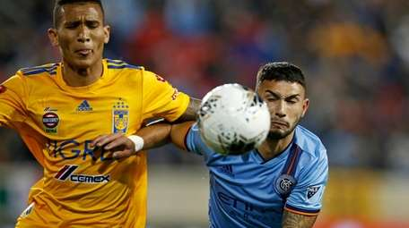 Tigres defender Francisco Meza, left, battles for the