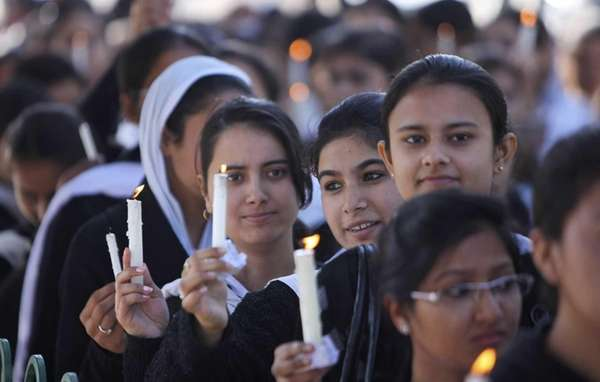 Indian students hold candles during a rally to
