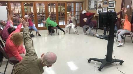 Seniors attend a chair yoga class last August