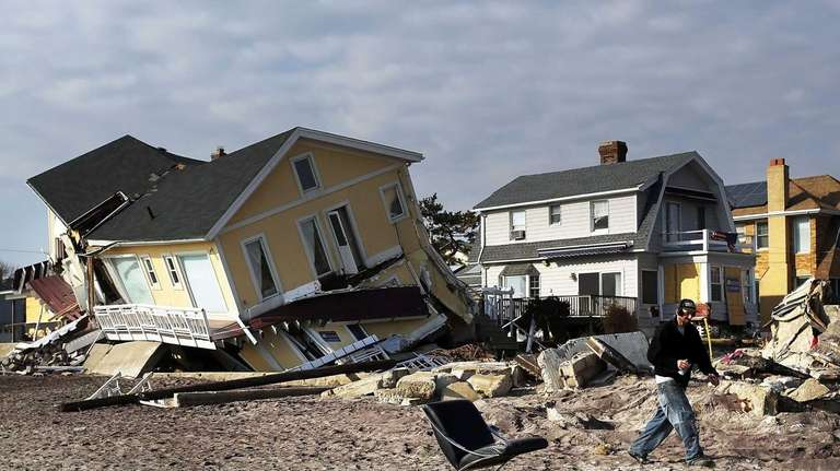A man walks by destroyed homes along the