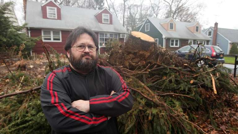 Richard Silverman stands beside a pile of tree