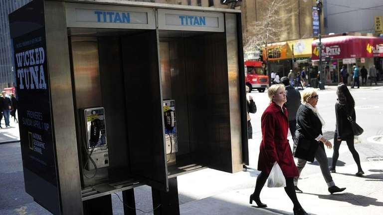 People walk by empty public pay phone booths
