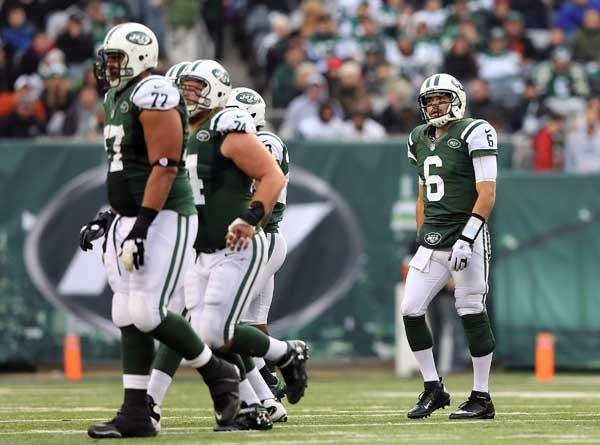 Mark Sanchez #6 and teammates walk of field.