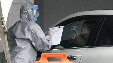A worker checks a woman's ID at New