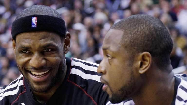 LeBron James talks with Dwyane Wade during the