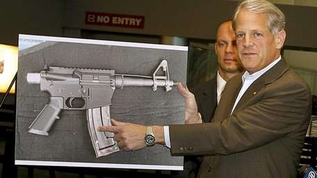 Holding up a photo of a plastic AR-15