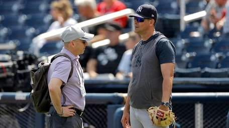 Brian Cashman, left, general manager of the New