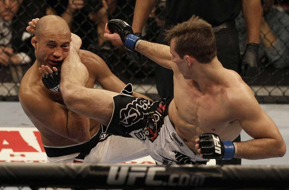 Rory MacDonald, right, kicks BJ Penn in the