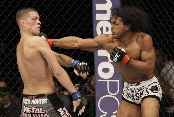 Ben Henderson, right, punches Nate Diaz during the