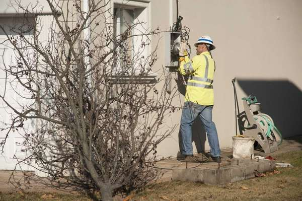 A utility worker places a plastic ring on