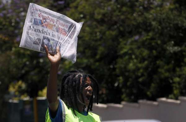 A newspaper vendor sells Sunday newspapers reporting on