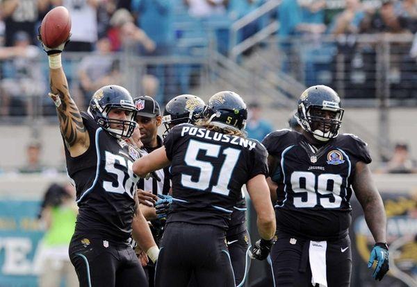 Jacksonville Jaguars defensive end Jason Babin, left, celebrates