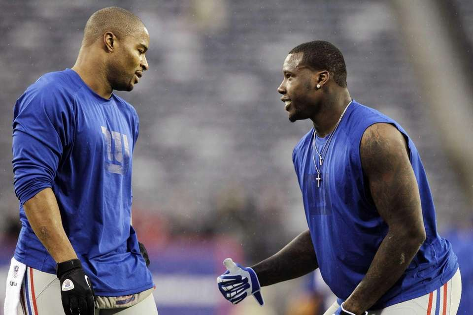 Jason Pierre-Paul, right, warms up with Osi Umenyiora,