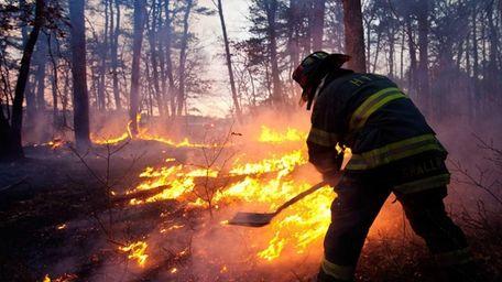 A firefighter battles a blaze off Wading River