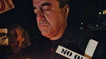 Enrique Morones holds a candle and a cross