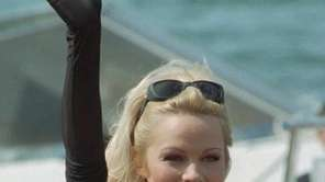 Actress Pamela Anderson waves during a photo session